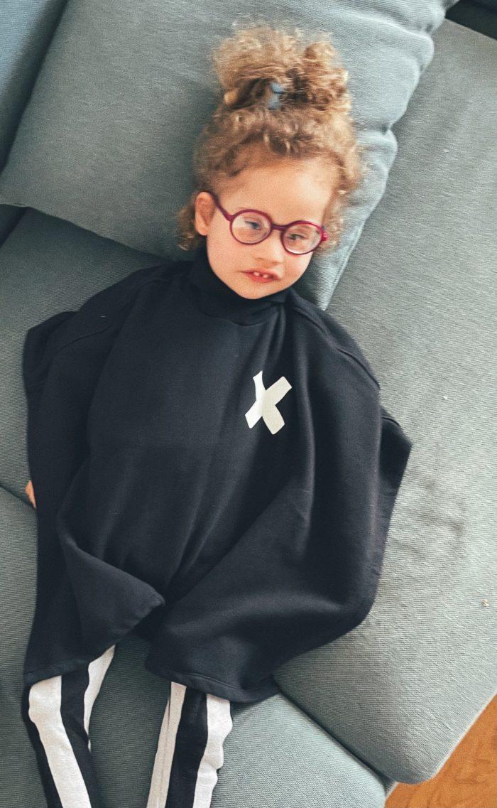 das Kind der Autorin, liegend auf der Couch im schwarzen Cape mit weißem Kreuz, in die Kamera blickend
